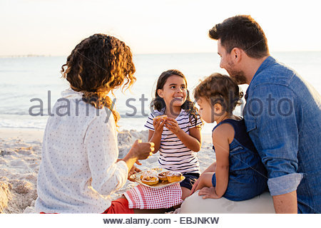 Couple with two girls having picnic on beach, Tuscany, Italy - Stock Photo