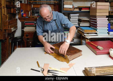 Senior man repairing antique book spine in traditional bookbinding workshop - Stock Photo