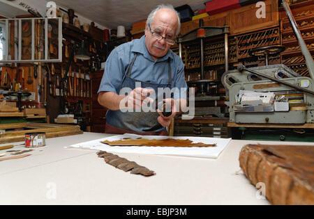 Senior man repairing fragile book spine in traditional bookbinding workshop - Stock Photo