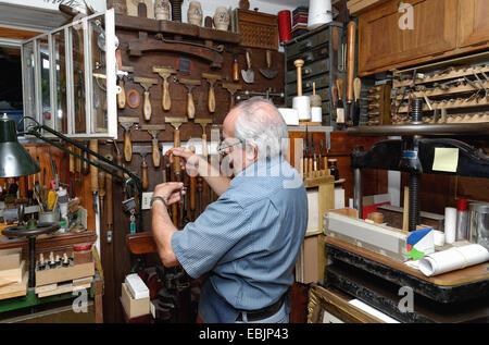 Senior man selecting tools in traditional bookbinding workshop - Stock Photo