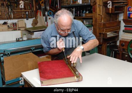 Senior man restoring book in traditional bookbinding workshop - Stock Photo