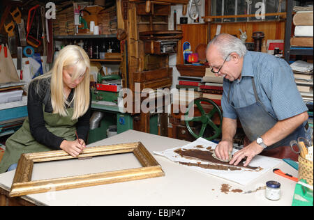 Senior man and young woman restoring picture frame and book spine in traditional bookbinding workshop - Stock Photo