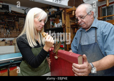 Senior man and young woman applying gold leaf to book spine in traditional bookbinding workshop - Stock Photo