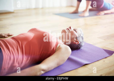 Mature woman lying on back in pilates class - Stock Photo