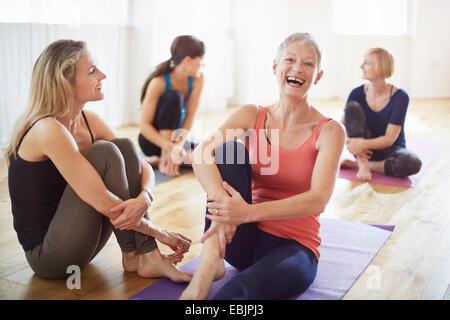 Four women sitting on floor in pilates class - Stock Photo