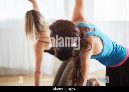 Two women kneeling and raising arms in pilates class - Stock Photo