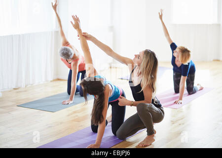 Women kneeling and raising arms in pilates class - Stock Photo