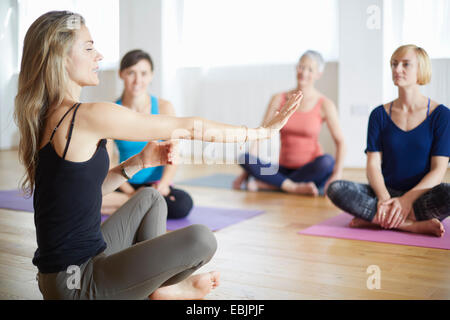 Mature female tutor with arms outstretched in pilates class - Stock Photo