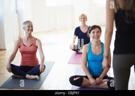 Female students watching and listening to tutor in pilates class - Stock Photo