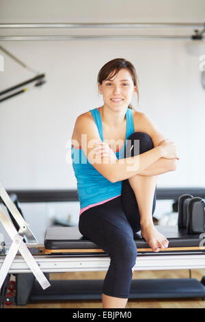 Portrait of young woman sitting on reformer in pilates gym - Stock Photo