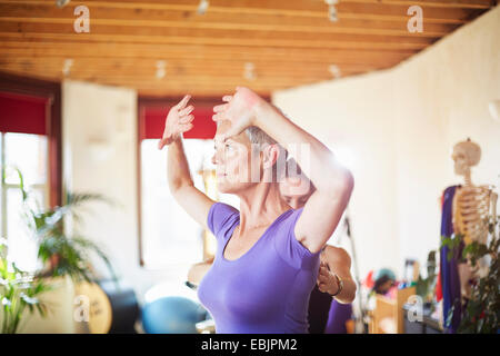 Mature female student and tutor in pilates gym - Stock Photo