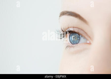 Studio close up of mid adult womans gazing blue eye - Stock Photo
