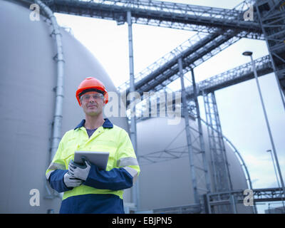 Portrait of worker holding digital tablet at biomass facility - Stock Photo
