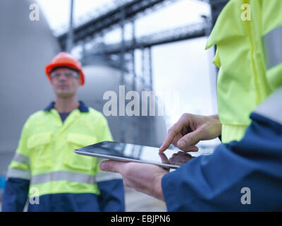 Workers using digital tablet at biomass facility, close up - Stock Photo
