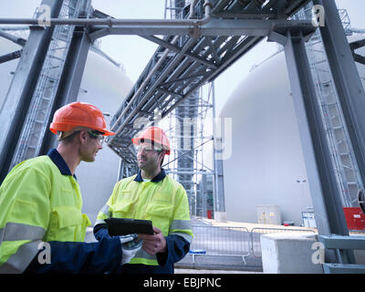 Workers using digital tablet at biomass facility - Stock Photo