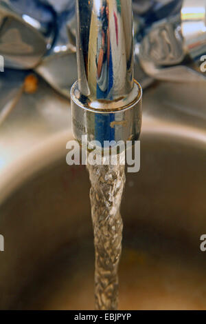 water running into the sink in the kitchen, Germany - Stock Photo