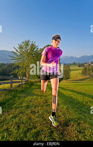 young woman trail running in a meadow and forest landscape, Austria, Styria, Dachstein - Stock Photo