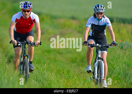 young couple going through meadows by mountainbike, Germany, Baden-Wuerttemberg - Stock Photo