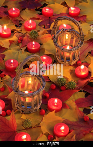 burning tea candles and two lanterns in autumn foliage - Stock Photo