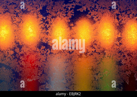 frost flowers on window in candle light - Stock Photo
