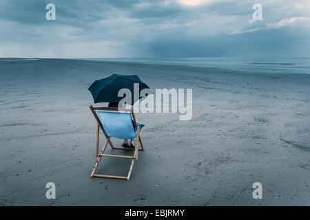 mature woman sitting on deck chair on stormy beach, under umbrella - Stock Photo