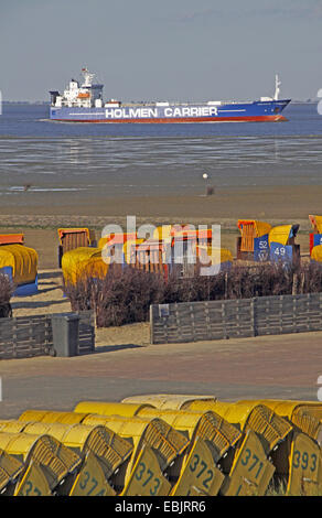 roofed wicker beach chairs on sandy beach, cargo ship in background, Germany, Lower Saxony, Cuxhaven - Stock Photo