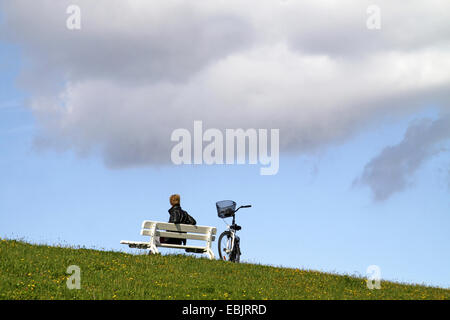 woman sitting on a bench on dyke, bicycle beside her, Germany, Lower Saxony, Cuxhaven - Stock Photo