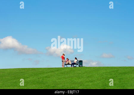 three woman sitting on a bench on the North Sea dyke, Germany, Lower Saxony, Cuxhaven, Dorum-Neufeld - Stock Photo