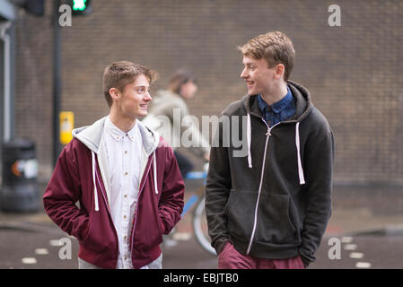Two male friends crossing road - Stock Photo