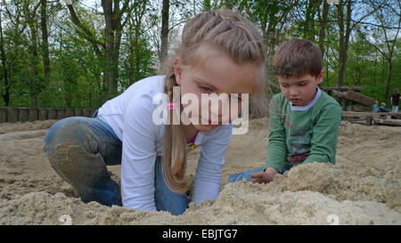 little boy and little girl playing in the sand on a playground - Stock Photo