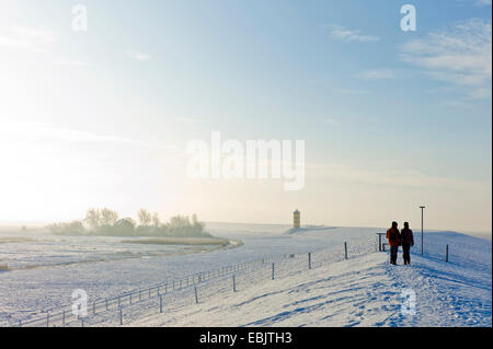 two persons on a dike with Pilsum lighthouse in winter in the background, Germany, Lower Saxony, East Frisia, Pilsum - Stock Photo