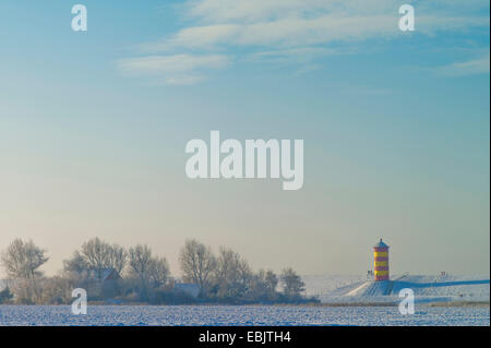 two persons at Pilsum lighthouse in winter, Germany, Lower Saxony, East Frisia, Pilsum - Stock Photo