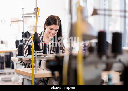 Young female seamstress using sewing machine in workshop - Stock Photo
