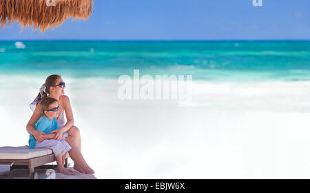 mother and son sitting at tropical beach, Mexico, Tulum - Stock Photo