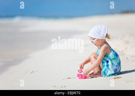 little girl playing with toys at tropical beach, Mexico - Stock Photo