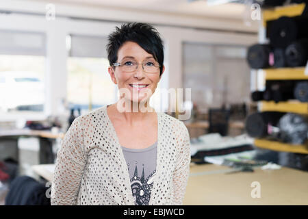 Portrait of mature seamstress in workshop - Stock Photo