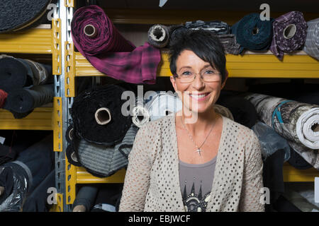 Portrait of mature seamstress in front of rolls of textile in workshop - Stock Photo
