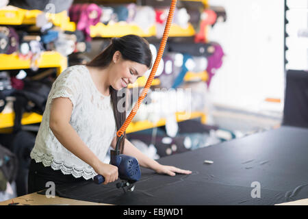 Young seamstress using cutting machine on textile at work table - Stock Photo