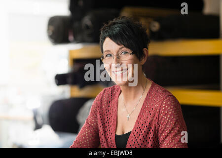 Portrait of mature seamstress in front of textile rolls in workshop - Stock Photo