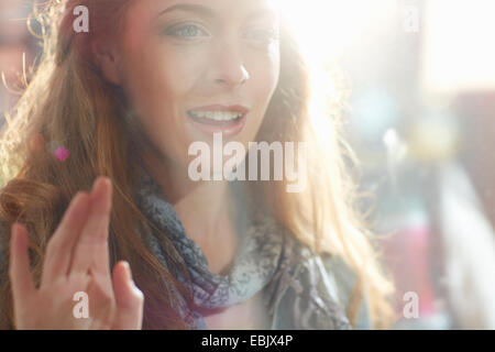 Young woman looking in shop window - Stock Photo