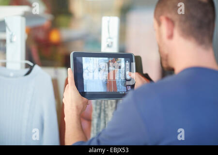 Mid adult man holding digital tablet, taking photograph of shop window - Stock Photo