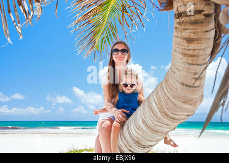 mother and daughter sitting on palm the beach, Mexico - Stock Photo