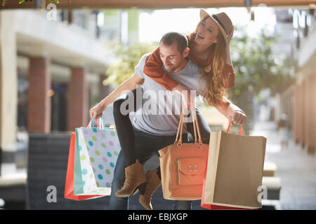 Man carrying woman on back, holding shopping bags - Stock Photo