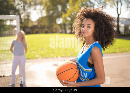 Portrait of young woman holding basketball - Stock Photo