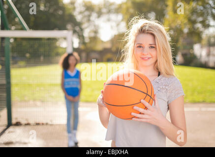 Portrait of young woman holding up basketball - Stock Photo