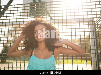 Portrait of young female basketball player with hands in hair - Stock Photo