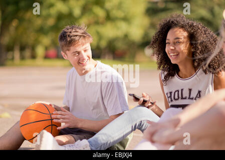 Group of young adult basketball players sitting chatting - Stock Photo