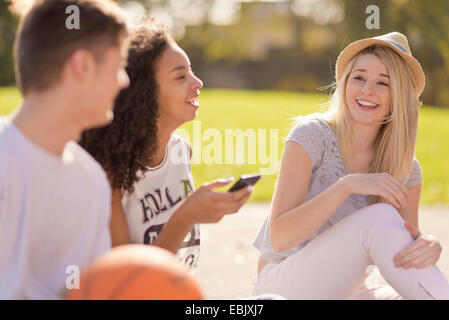Three young adult basketball players chatting and laughing - Stock Photo