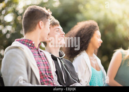 Four young adult friends sitting talking in park - Stock Photo