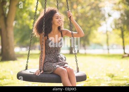 Portrait of young woman sitting on tire swing - Stock Photo